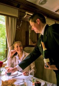 luxury tour peru, a waiter serving a glass of wine in a luxurious train